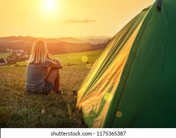 Happy woman with open arms sitting near tent around mountains under sunset light sky enjoying the  leisure and freedom.