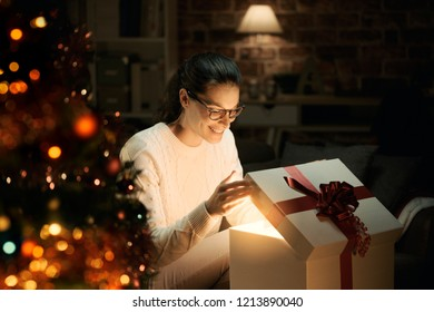Happy woman opening a magical shiny Christmas gift at home, Christmas tree in the foreground