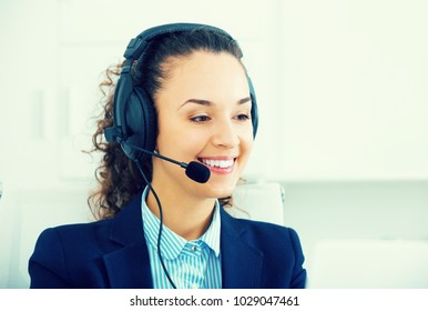 Happy woman operator talking with client by headset and smiling