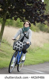 Happy woman outdoors on blue bicycle