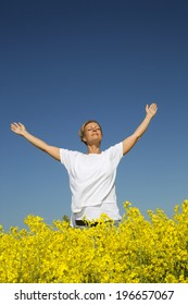 Happy Woman with Outstretched arms on a Rape Field