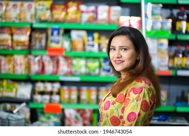 Happy woman owner with arms crossed at grocery aisle of supermarket
