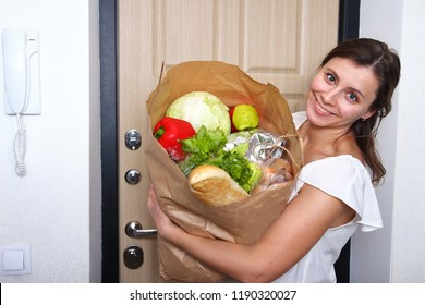 Happy woman with paper bag of vegetables and food from grocery store on door background at home