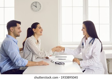 Happy woman patient giving gratitude handshake to doctor get good news about pregnancy on appointment at clinic office. Satisfied caucasian family couple visit physician for healthcare consultation