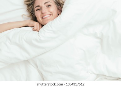 Happy woman peeking from under bed covers