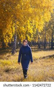 happy woman pensioner walking in autumn Park in autumn