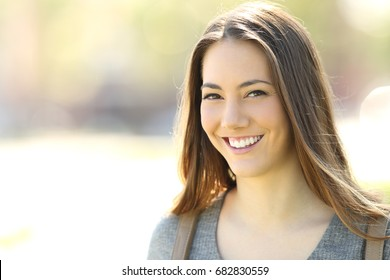 Happy woman with perfect smile looking at camera outdoors in the street