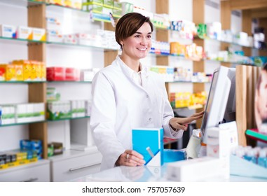 Happy woman pharmacist ready to assist in choosing at counter in pharmacy