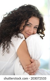 Happy woman with the pillow in white bed