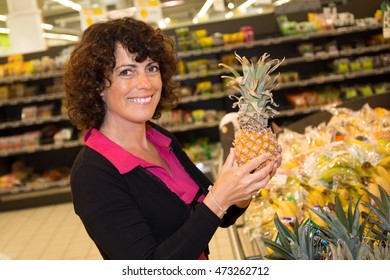 Happy woman with pineapple fruit in supermarket