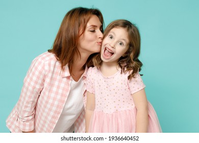Happy woman in pink clothes have fun with cute child baby girl 5-6 years old. Mommy little kid daughter kiss on cheek isolated on pastel blue azure background studio. Mother's Day love family concept