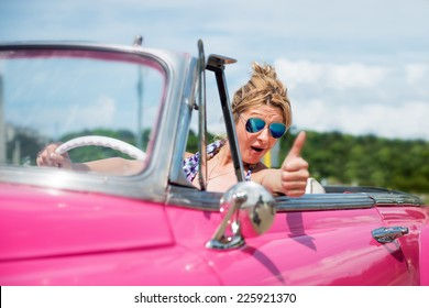 Happy woman in a pink convertible car, cabriolet, looking at camera, thumb up