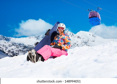 Happy woman in pink sit in snow with snowboard with cable car and mountains on blue sky background