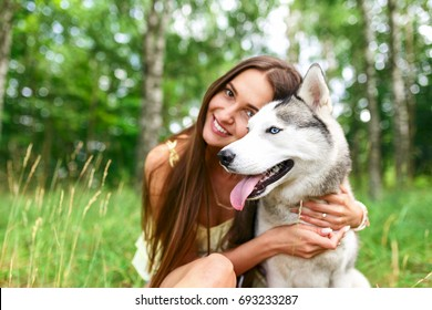 Happy woman  playing with her dog in the yard of the house in spring. Siberian husky.