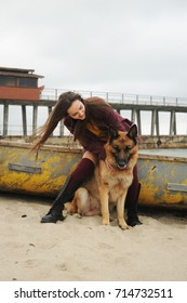 Happy woman playing with her German shepherd dog outdoor