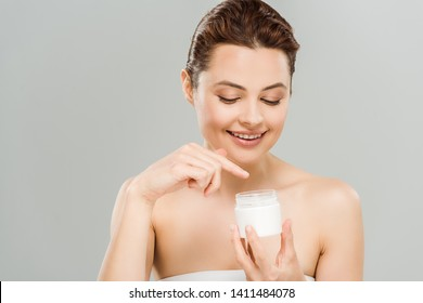 happy woman pointing with finger at container with face cream isolated on grey