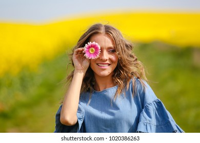 Happy woman posing with flowers  in the vast field of canola flowers