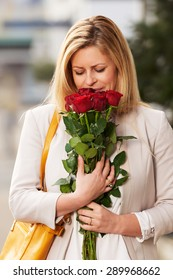 Happy woman posing smelling a bouquet of roses with yellow handbag on shoulder