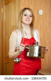 Happy woman with  pot at her kitchen