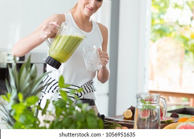 Happy woman pouring a green cocktail into a cup during detox diet