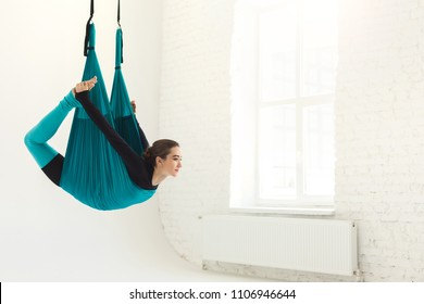 Happy woman practicing fly yoga asana over white background in fitness studio, copy space. Health, sport, yoga concept