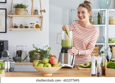 Happy woman preparing healthy green smoothie in her kitchen