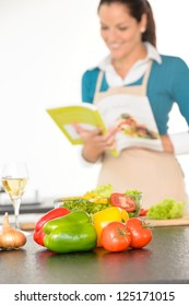 Happy woman preparing recipe vegetables wine kitchen cooking book