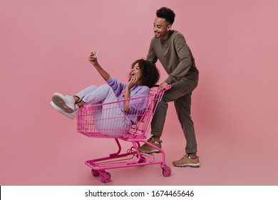 Happy woman in purple outfit sitting in shopping cart and taking selfie with friend. Brunette dark-skinned girl holds cell-phone and poses with handsome man on pink background