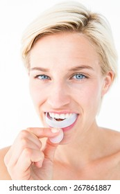 Happy woman putting her gum shield on white background