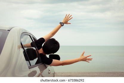 Happy woman raised arms from the car parked in the sea on a bright day. Vintage picture.