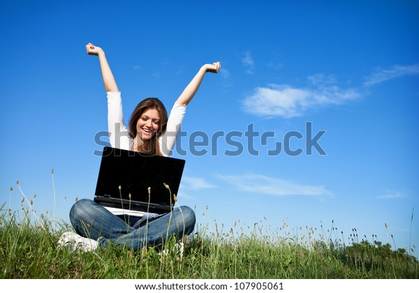 Happy woman with raised arms at a laptop, outdoor