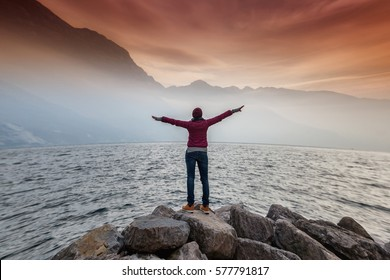Happy woman raised her arms up and enjoy view of magnificent landscape. Lake Garda Italy