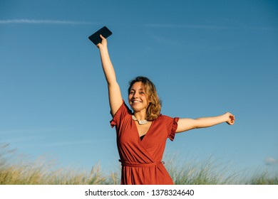 Happy woman raising arms for celebrating mobile phone coverage on summer vacation at the beach.