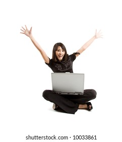 A happy woman raising her arms while working on her laptop
