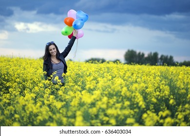 Happy woman at the rape field with balloons
