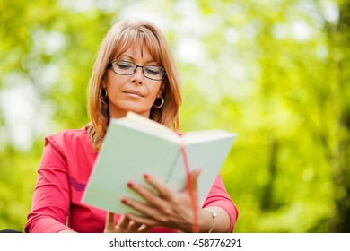 Happy woman reading a book during springtime in nature.