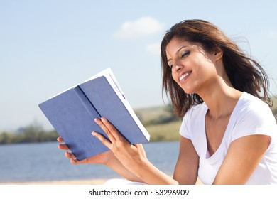 happy woman reading book outdoors