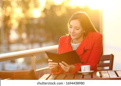 Mujer feliz leyendo un libro en un lector sentado en un balcón al atardecer