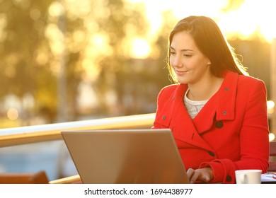 Mujer feliz leyendo en un ordenador portátil al atardecer sentada en un balcón