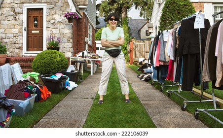 happy woman ready to sell items at yard sale.