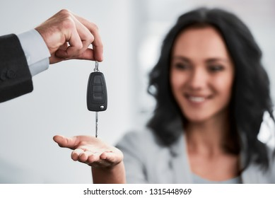 Happy woman receives the keys to a new car from a sales manager.