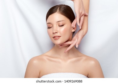 happy woman receiving massage for her face with eyes closed, beautician doing massage, healthy and fresh girl in spa