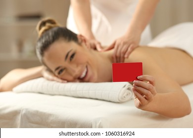Happy woman receiving a massage showing blank credit or gift card in a spa salon
