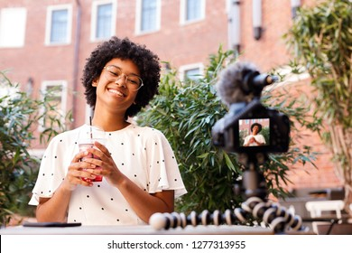 Happy woman recording a video on dslr camera, holding a juice
