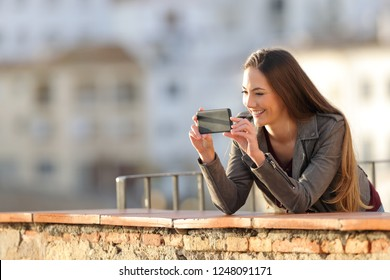 Happy woman recording videos or taking photos with smart phone in a balcony at sunset