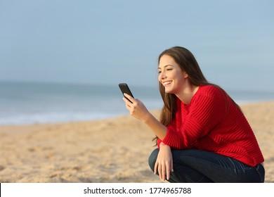 Mujer feliz de rojo revisando el contenido de los teléfonos inteligentes sentada en la playa