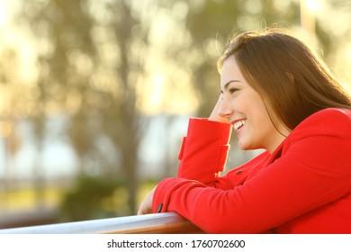 Mujer feliz con abrigo rojo mirando lejos en un balcón cerca de la playa al atardecer