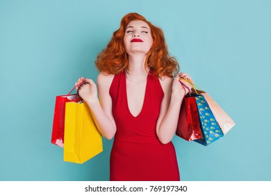 Happy woman in red dress with shopping bags on a blue background.