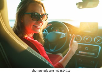 Happy woman in red dress with thumb up sitting in car. The concept of buying or renting a car