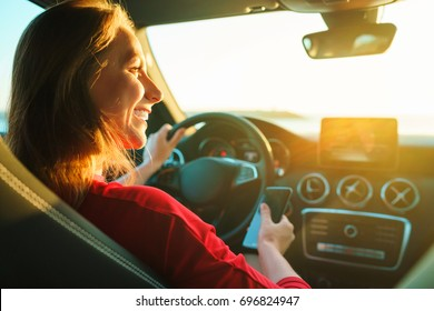 Happy woman in red dress uses a smartphone while driving a car at sunset